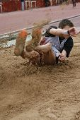 pic of broad-bodied  - athletic long jumper landing sand flying around  - JPG