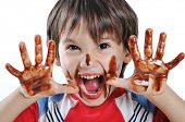 Chocolate on hands and face, funny cute boy