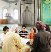 Muslim people teaching and learning inside the mosque, man, woman and children together reading Kora