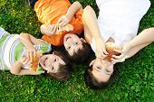 stock photo of eat grass  - Three children laying on green grass on ground and eating sandwiches and smiling - JPG