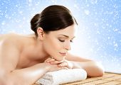 Beautiful, young and healthy woman in winter spa salon. Massage treatment over Christmas background  poster