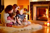 Happy Family Using A Tablet Pc By A Fireplace poster
