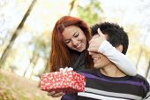 woman covering the eyes to his boyfriend with giving him a present (selective focus with shallow DOF