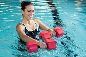 Fit woman working out with foam dumbbell in swimming pool. Woman engaged in doing aqua aerobics in w poster