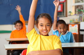 pic of school child  - Three cheerful young primary school children indicating they know the answer with hands raised in class - JPG