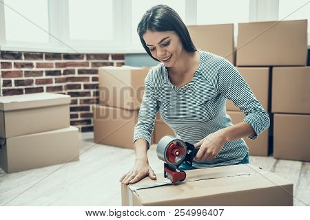 poster of Young Smiling Woman Packing Cardboard Box At Home. Happy Beautiful Girl Preparing To Relocation By P