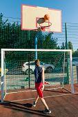Teenager Boy Street Basketball Player On The City Basketball Court poster