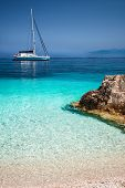 Beautiful Calm Azure Blue Lagoon With Sailing Catamaran Yacht Boat At Anchor. Pure White Pebble Beac poster