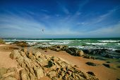 Sea Waves Lash Line Impact Stone On The Beach. Rocky Coastline With Sandand  Beauty Ocean, Blue Sky poster