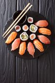Sushi Rolls Set Served On Black Stone Slate On Dark Background. Vertical Top View poster