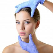 Beauty treatment for young beautiful female face, doctors hand in gloves touch face of woman isolat poster