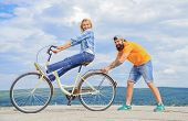 Woman Rides Bicycle Sky Background. Man Helps Keep Balance And Ride Bike. How To Learn To Ride Bike  poster