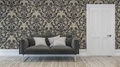 Dark gray sofa chair with three pillows in room with paisley brown tone wallpaper in background over poster