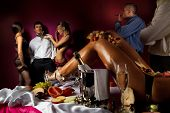 stock photo of bachelor party  - Guys having fun with woman decorated  by fruits and dancing stripteasers - JPG