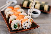 Eating Sushi. Food Photo, Japanese Restaurant, Dinner. Pair Of Chopsticks Taking Sushi Roll From Pla poster