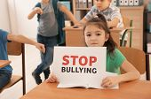 Little girl with sign Stop bullying in classroom poster