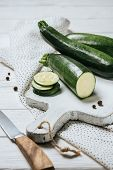 Cut And Whole Green Zucchini On White Wooden Table poster