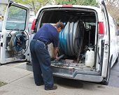stock photo of vacuum pump  - carpet cleaning tech getting equipment ready - JPG