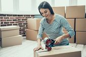 Young Smiling Woman Packing Cardboard Box At Home. Happy Beautiful Girl Preparing To Relocation By P poster