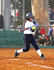 pic of fastpitch  - Fastpitch softball female batter hitting the ball at the plate - JPG