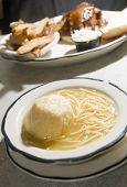 pic of matzah  - bowl of matzoh matzah ball soup rice noodles brisket barbecue sandwich in background - JPG