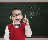 stock photo of lightbulb  - Portrait of male elementary school student with lightbulb picture on blackboard - JPG