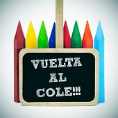 sentence back to school written in spanish, vuelta al cole, in a blackboard label and some crayons o