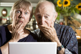 stock photo of pornography  - Perplexed Senior Couple in their Dining Room with a Laptop Computer - JPG