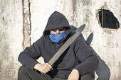 picture of machete  - Man with a machete leaning against old wall - JPG