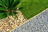 stock photo of stone house  - Landscaping combinations of grass plant and stones - JPG