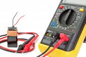 Electrical Multimeter To Check The Resistance. On A White Background With Battery.