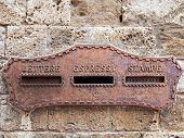 stock photo of mailbox  - old italian mailbox oxidized in the wall - JPG