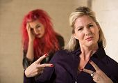 picture of embarrassing  - Cool mother making hand gesture with embarrassed teenager - JPG