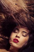 stock photo of flowing hair  - A beauty shot of a young woman with red lips and flowing hair over dark background - JPG