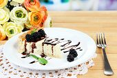 pic of cheesecake  - Slice of cheesecake with chocolate sauce and blackberry on plate - JPG