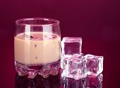 stock photo of bailey  - Baileys liqueur in glass on pink background - JPG