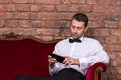 stock photo of settee  - Conceptual image of an elegant businessman lying relaxing on a settee against a brick wall and reading tablet - JPG