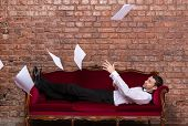 picture of settee  - Conceptual image of an elegant businessman lying relaxing on a settee against a brick wall with flying paperwork floating in the air above him - JPG