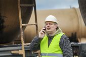 Railroad employee with cell phone near tank wagons