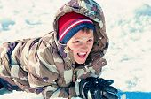 image of inflatable slide  - cute boy in camo jacket laying in the snow - JPG
