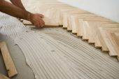 stock photo of wood pieces  - Carpenter on work putting wood parquet pieces - JPG