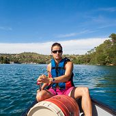 stock photo of canoe boat man  - Handsome young man on a canoe on a lake - JPG