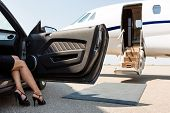 stock photo of superstars  - Low section of wealthy woman stepping out of car parked in front of private plane - JPG