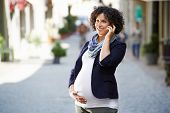 stock photo of people talking phone  - Happy people and lifestyle with pregnant woman talking with cell phone in city street