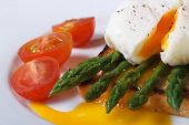 stock photo of benediction  - Toast with asparagus egg Benedict and tomatoes on a white plate macro. horizontal