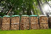 stock photo of firewood  - Dry chopped firewood logs in a pile covered with nylon sleeve in a green forest - JPG