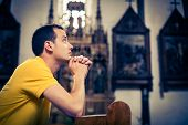 picture of church  - Handsome young man praying in a church - JPG