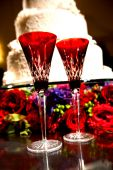 image of red rose flower  - Image of 2 beautiful red champagne toasting flutes by the cake at a wedding - JPG