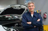 stock photo of auto garage  - Portrait Of Satisfied Auto Mechanic With Arm Crossed In Garage - JPG