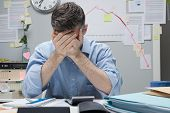 image of nervous breakdown  - Desperate office worker with head in hands and negative financial chart on background - JPG